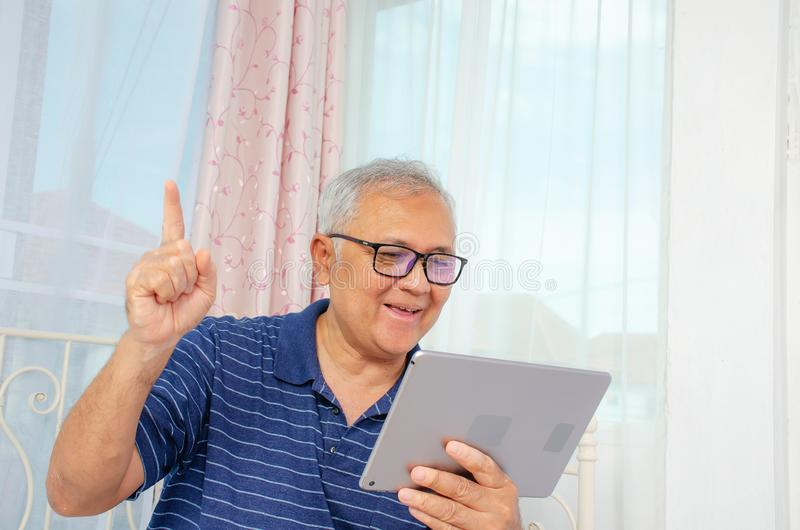 Portrait of smiling senior man reading news on digital tablet. Cheerful excited mature male using portable computer at home. Copy space royalty free stock photo