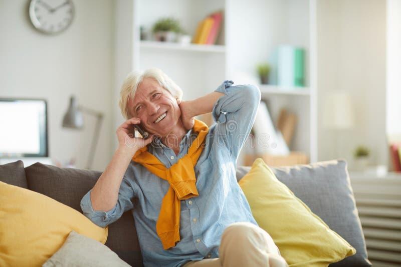 Smiling Senior Man Speaking by Phone at Home royalty free stock image