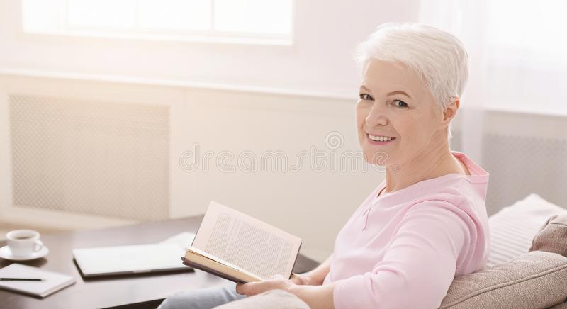 Portrait of smiling senior woman with book on sofa at home stock photos