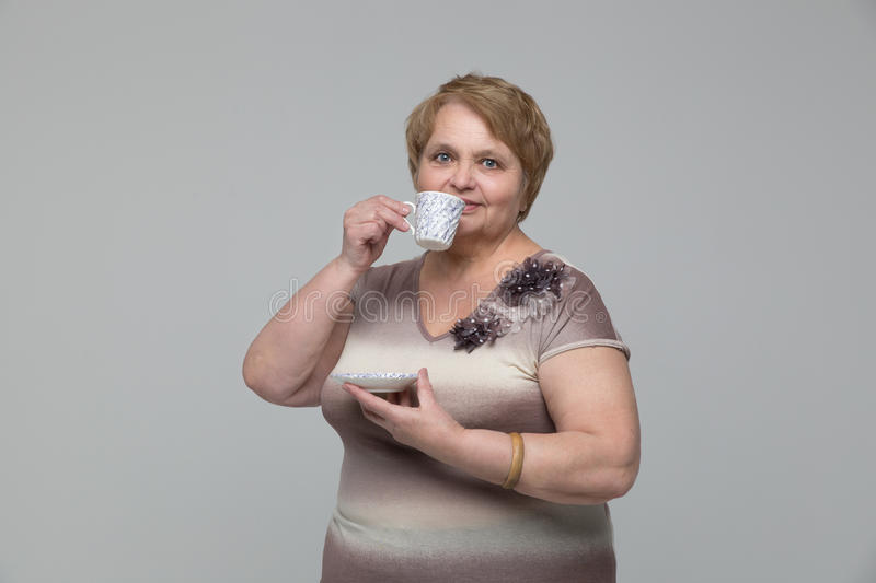 Portrait of smiling senior woman drinking tea royalty free stock images