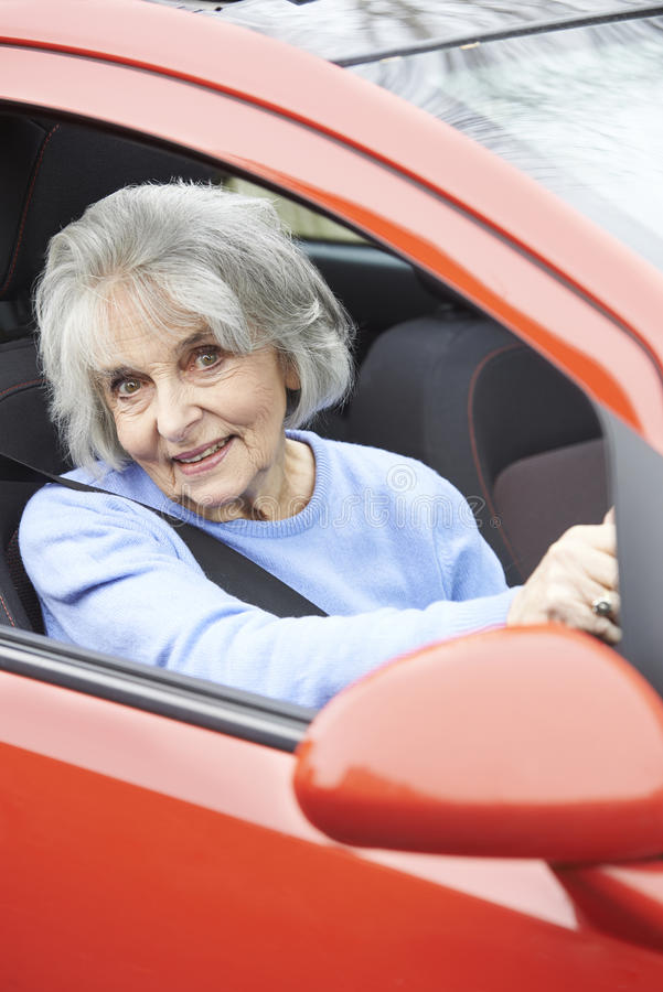Portrait Of Smiling Senior Woman Driving Car. Portrait Of Senior Woman Driving Car royalty free stock images