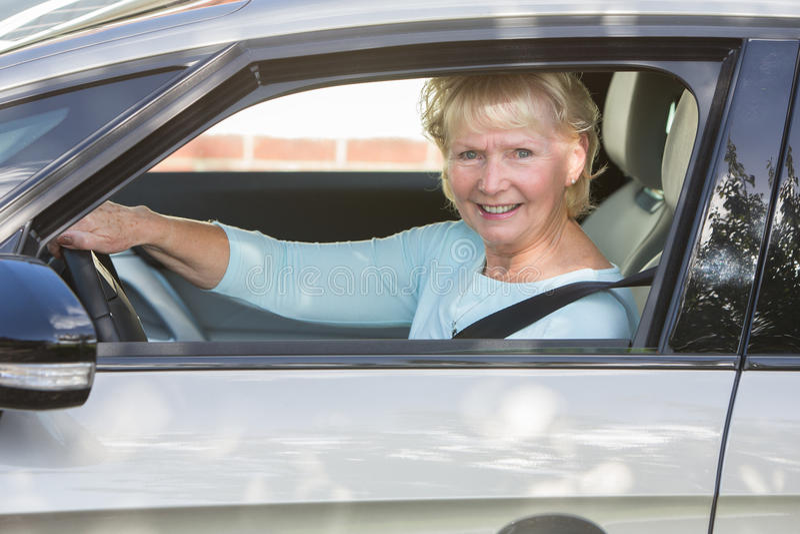 Portrait Of Smiling Senior Woman Driving Car. Smiling Senior Woman Driving Car royalty free stock images