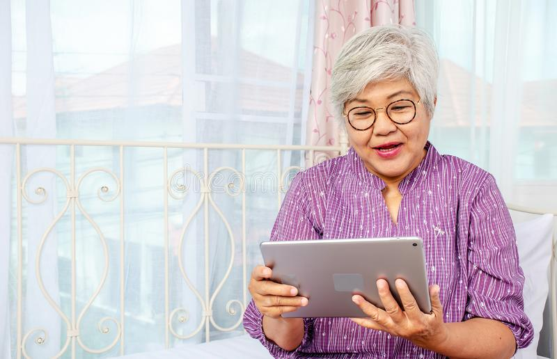 Portrait of smiling senior woman with eyeglasses using electronic tablet while relaxing at the bed room royalty free stock image