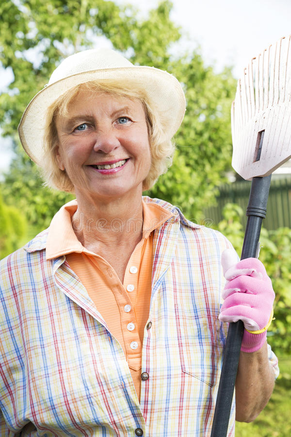 Portrait of a smiling senior woman in garden royalty free stock photography