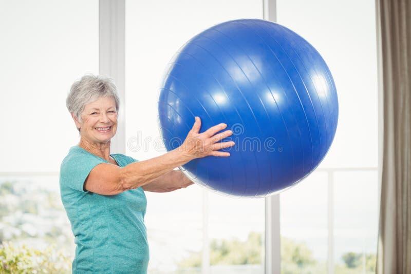 Portrait of smiling senior woman holding exercise ball stock photo