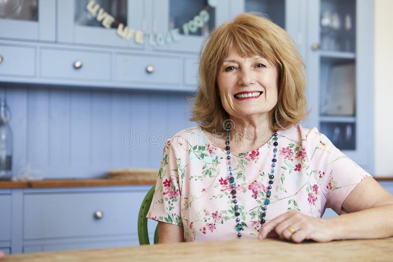 Portrait Of Smiling Senior Woman At Home Sitting At Table royalty free stock images