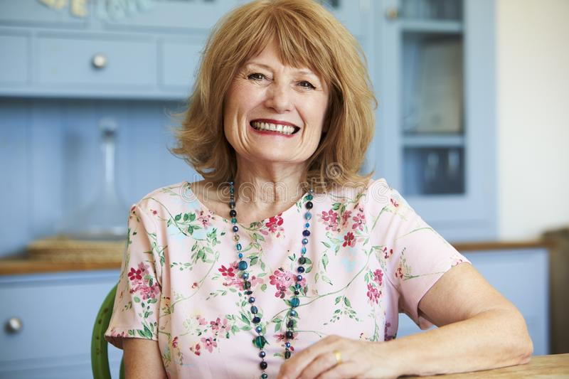 Portrait Of Smiling Senior Woman At Home Sitting At Table stock photo