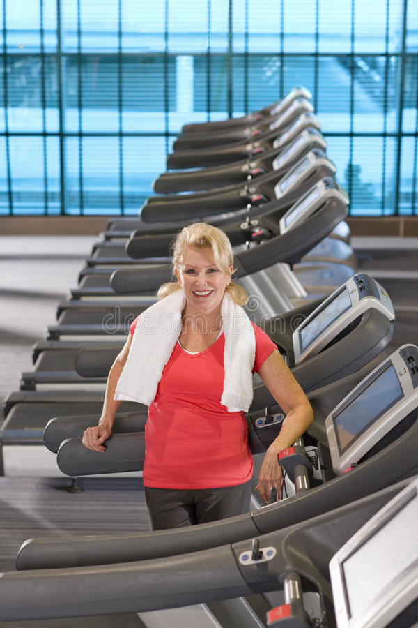 Portrait of smiling senior woman leaning on treadmill at health club stock image