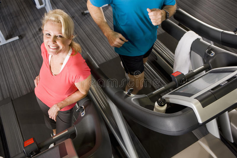 Portrait of smiling senior woman leaning on treadmill in health club. Portrait of smiling senior women leaning on treadmill in health club stock photo
