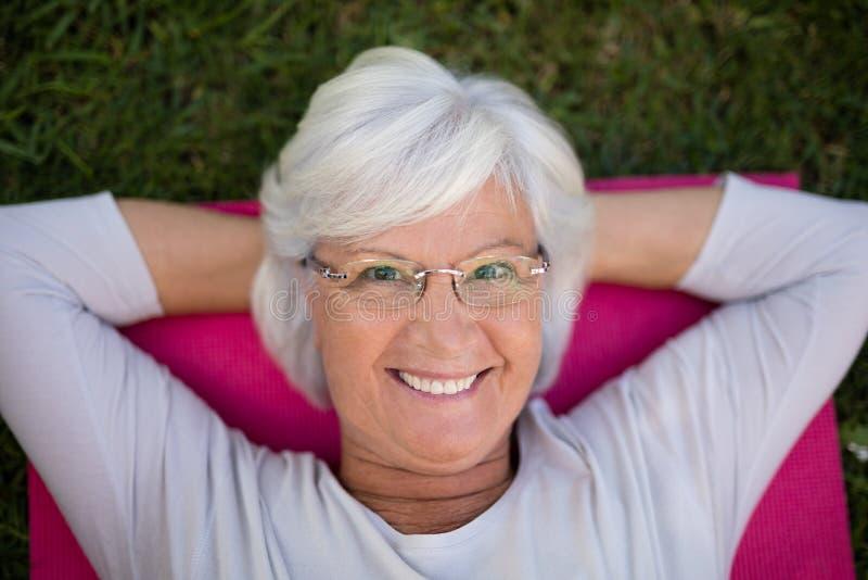 Portrait of smiling senior woman lying on exercise mat. High angle portrait of smiling senior woman lying on exercise mat at park royalty free stock image