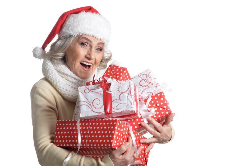 Portrait of smiling senior woman in Santa hat posing stock images