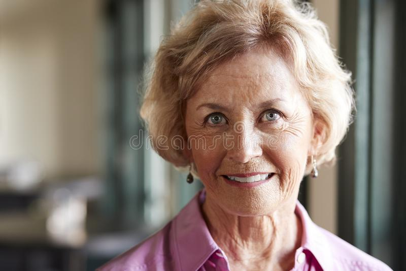 Portrait Of Smiling Senior Woman Sitting In Restaurant stock photography