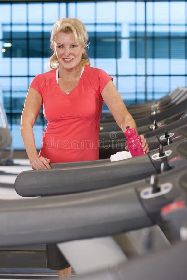 Portrait of smiling senior woman with water bottle on treadmill in health club royalty free stock images