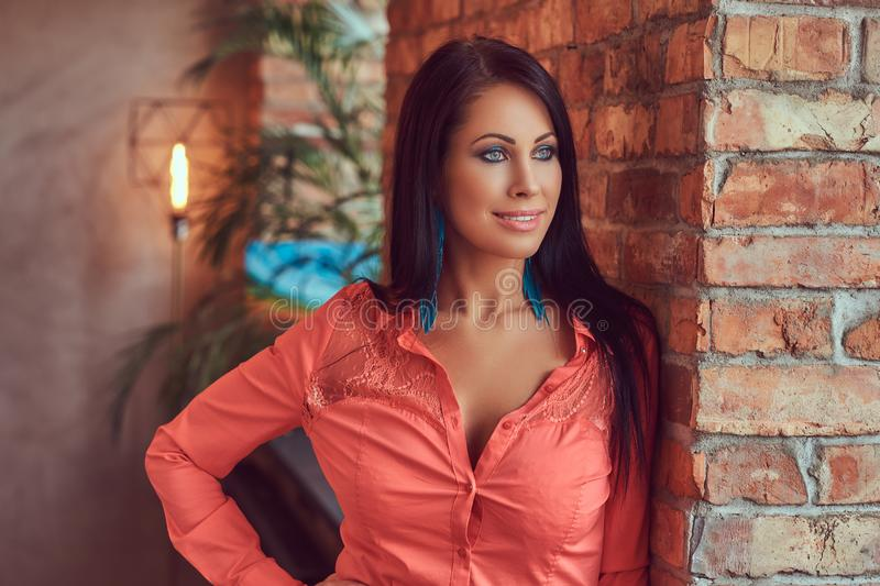 Portrait of a smiling sensual brunette in a bright blouse in a studio with a loft interior. stock photo