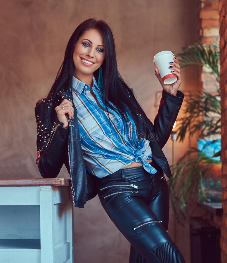 Portrait of a smiling sensual brunette posing in a stylish leather jacket and jeans leaning on a table holds a cup stock photography
