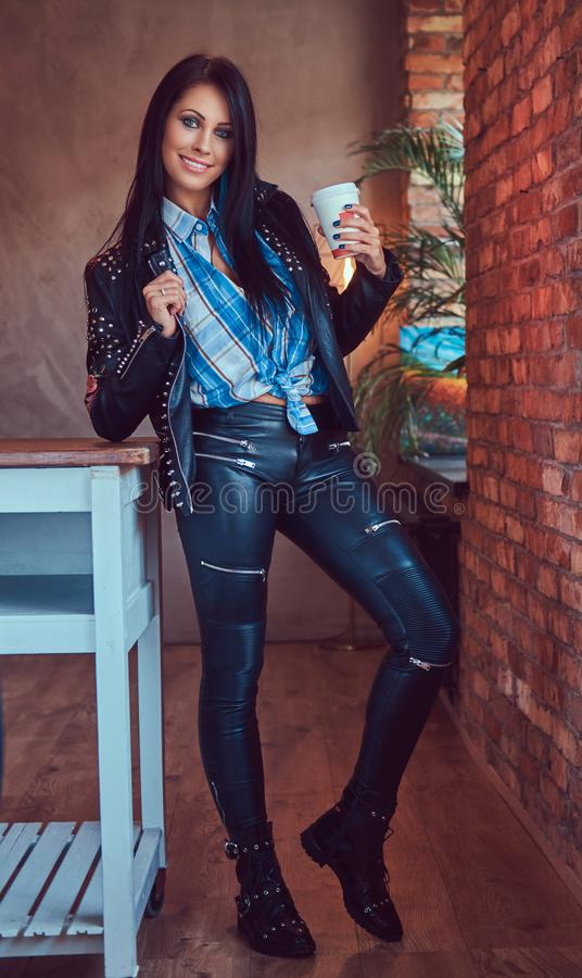 Portrait of a smiling sensual brunette posing in a stylish leather jacket and jeans leaning on a table holds a cup stock images