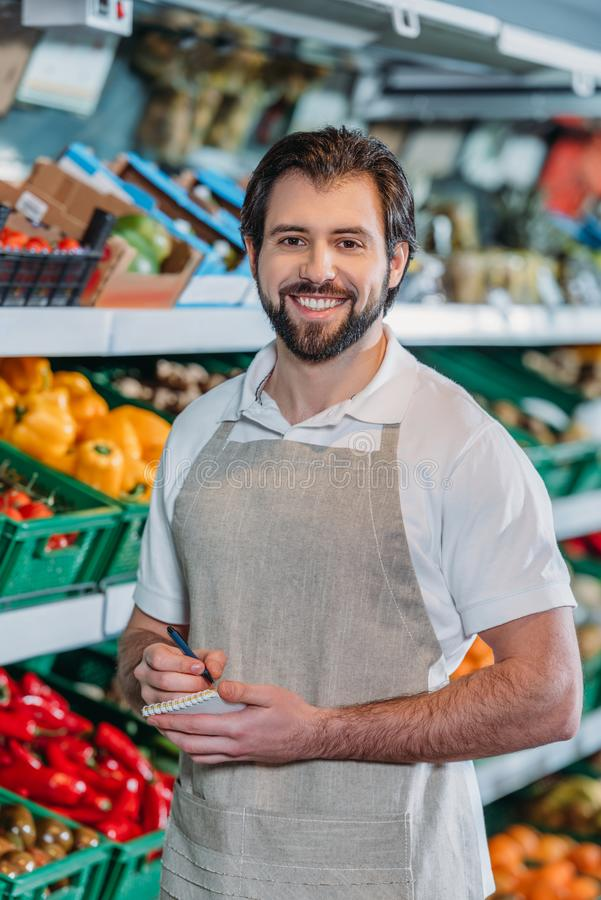 portrait of smiling shop assistant in apron with notebook royalty free stock images