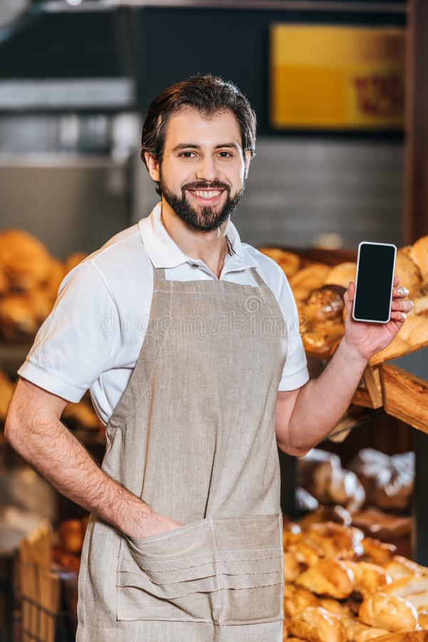 portrait of smiling shop assistant showing smartphone with blank screen stock photos