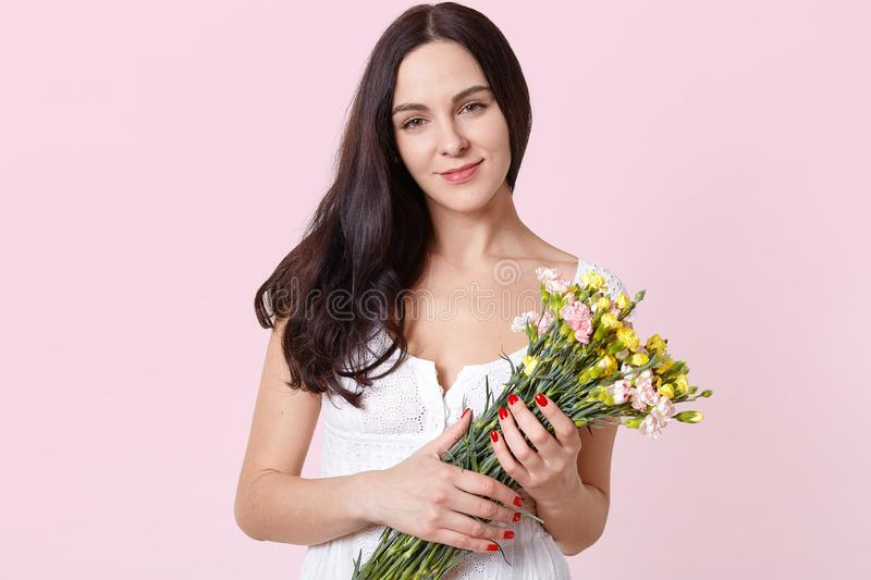 Portrait of smiling sincere young model standing isolated over light pink background, holding colourful spring flowers in hands, stock images