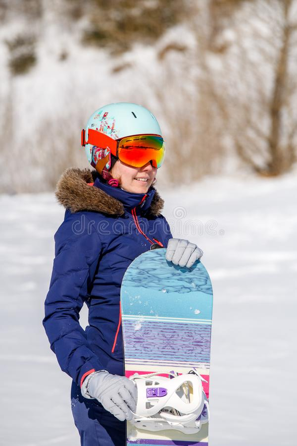 Portrait of smiling sportswoman in helmet with snowboard in winter day. On blurred background during day royalty free stock photo