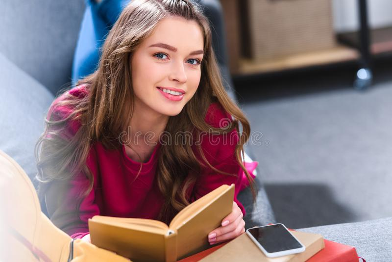 portrait of smiling student with book looking stock photo