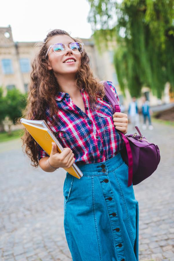portrait of smiling student in eyeglasses with notebooks running royalty free stock photo