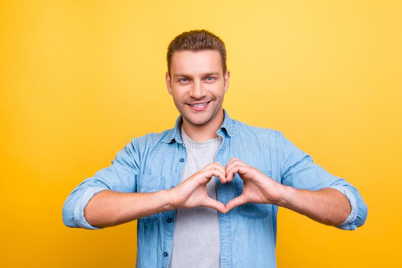 Portrait of smiling, stunning man with stubble showing heart fi stock images