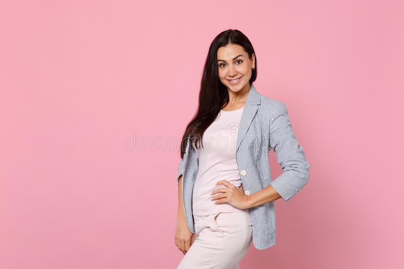 Portrait of smiling stunning young woman in striped jacket standing with arm akimbo on waist isolated on pink pastel royalty free stock photos