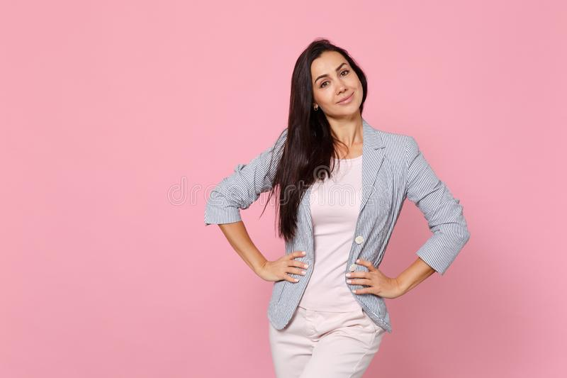 Portrait of smiling stunning young woman in striped jacket standing with arms akimbo on waist isolated on pink pastel. Wall background. People sincere emotions stock photos