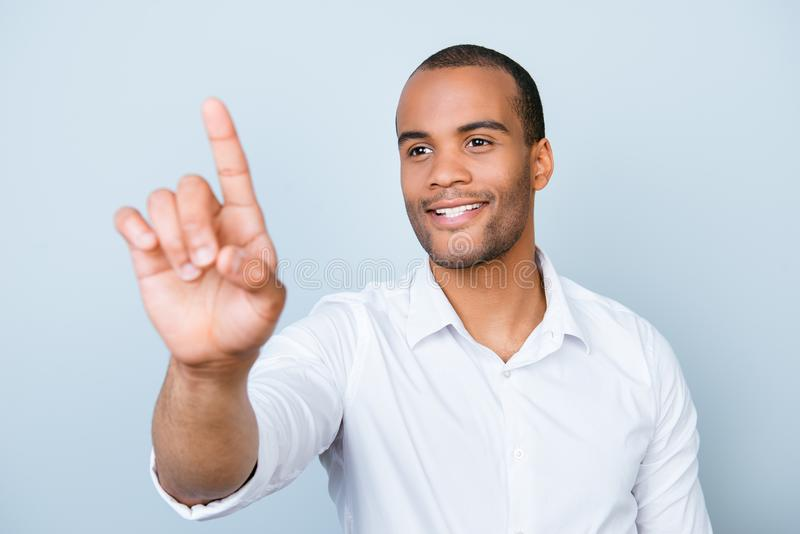 Portrait of smiling successful american mulatto entrepreneur touching virtual screen, standing on pure background, in white stock images