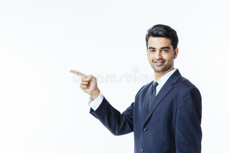 Portrait of a smiling, successful businessman in black suit and tie pointing to side royalty free stock images