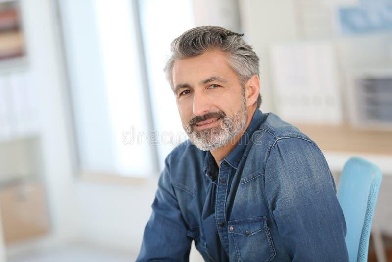 Portrait of smiling teacher sitting at desk in university office stock image