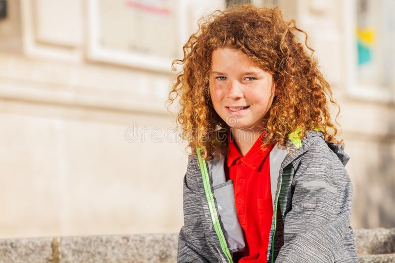 Teenage curly-haired boy looking at camera stock image