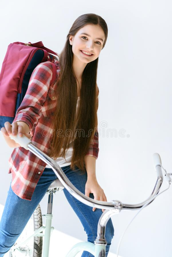 portrait of smiling teenage girl with backpack sitting on bicycle royalty free stock image