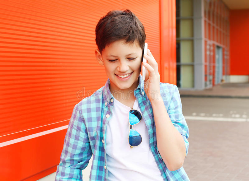 Portrait smiling teenager boy talking on the phone. In city royalty free stock images