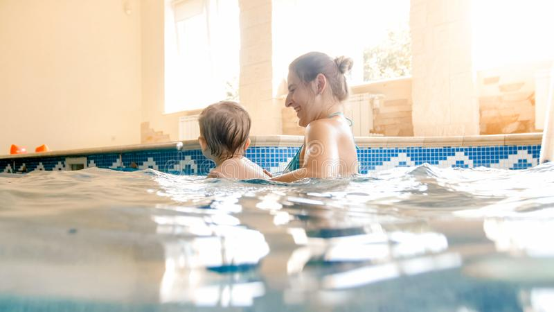 Portrait of happy smiling toddler boy learning swimming with mother in pool. Family having fun and relaxing in swimming. Portrait of smiling toddler boy learning royalty free stock image