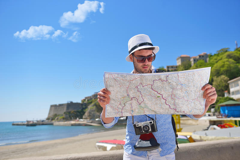 Portrait of a smiling tourist with map and bag royalty free stock photography