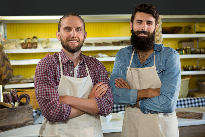 Portrait of smiling two male staff standing with arms crossed royalty free stock photo