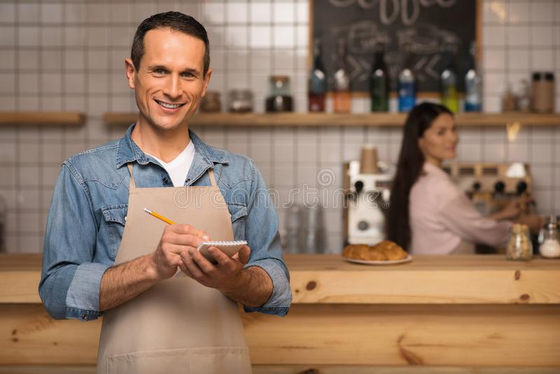 Waiter taking notes. Portrait of smiling waiter taking notes and looking at camera with waitress on the background royalty free stock image