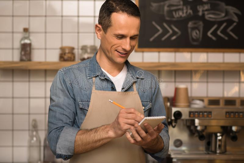 Waiter taking notes. Portrait of smiling waiter taking notes while working in cafe stock photo