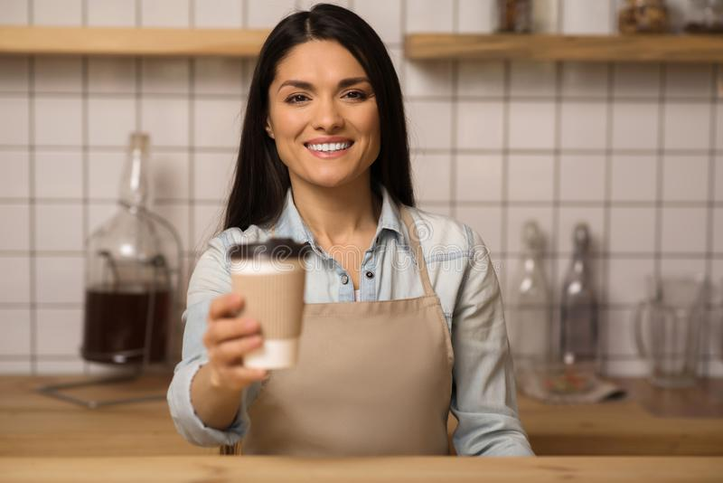 Waitress holding coffee to go. Portrait of smiling waitress holding coffee to go in paper cup and looking at the camera royalty free stock photos
