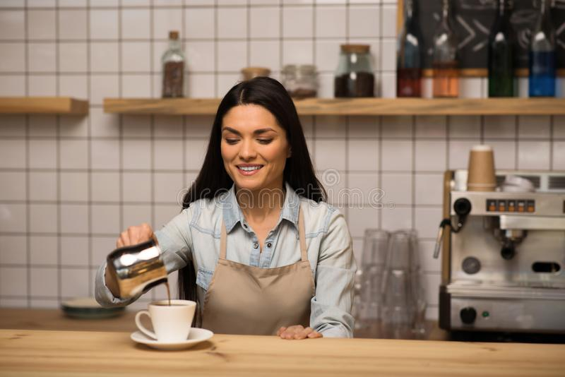 Waitress preparing coffee. Portrait of smiling Waitress preparing espresso pouring coffee into the cup royalty free stock image