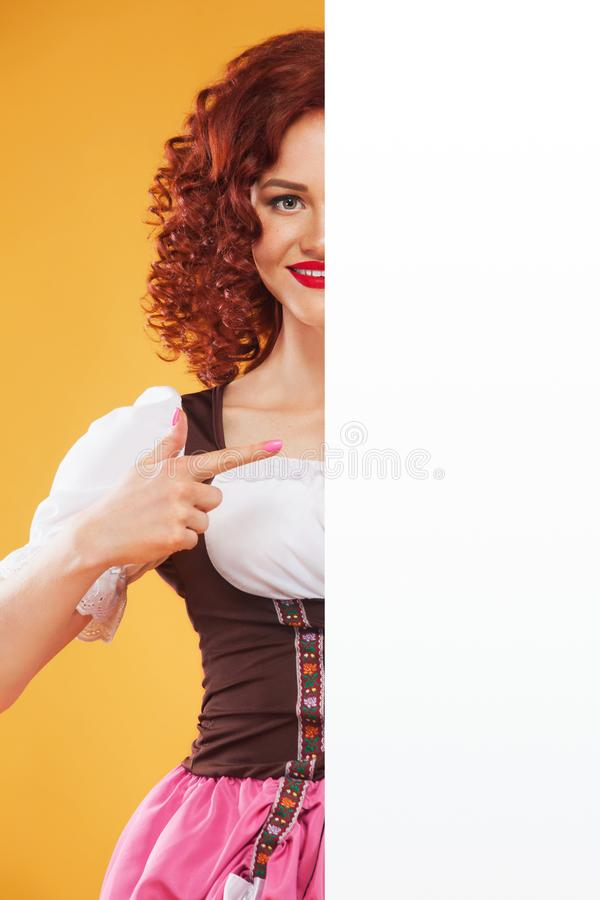 Portrait of smiling waitress standing with white banner signboard for copy space stock image