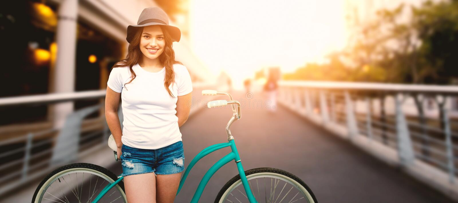 Composite image of portrait of smiling woman with bicycle. Portrait of smiling woman with bicycle against footbridge against sky in city royalty free stock photo