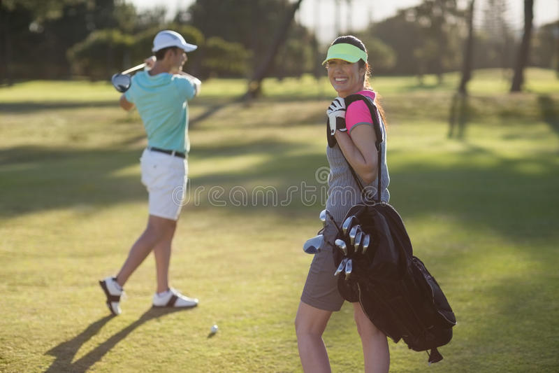 Portrait of smiling woman carrying bag with man playing golf. Portrait of smiling women carrying bag with men playing golf while standing on field royalty free stock images
