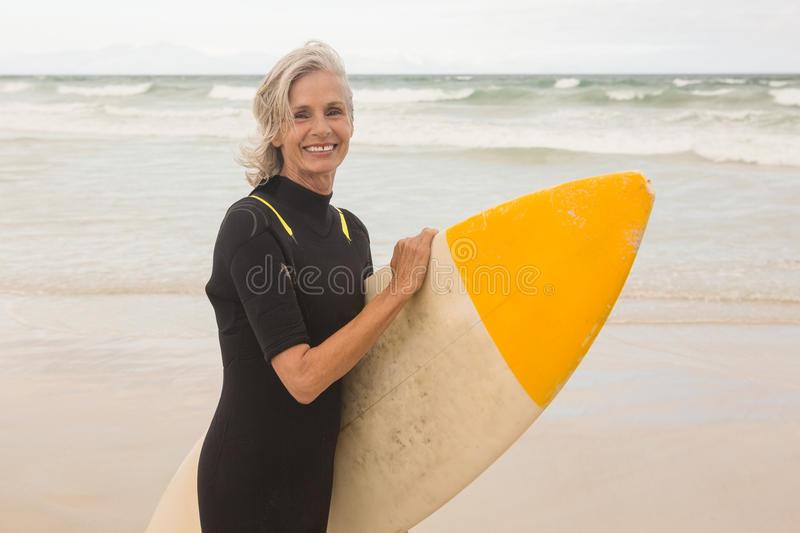 Portrait of smiling woman carrying surboard while standing on shore royalty free stock images