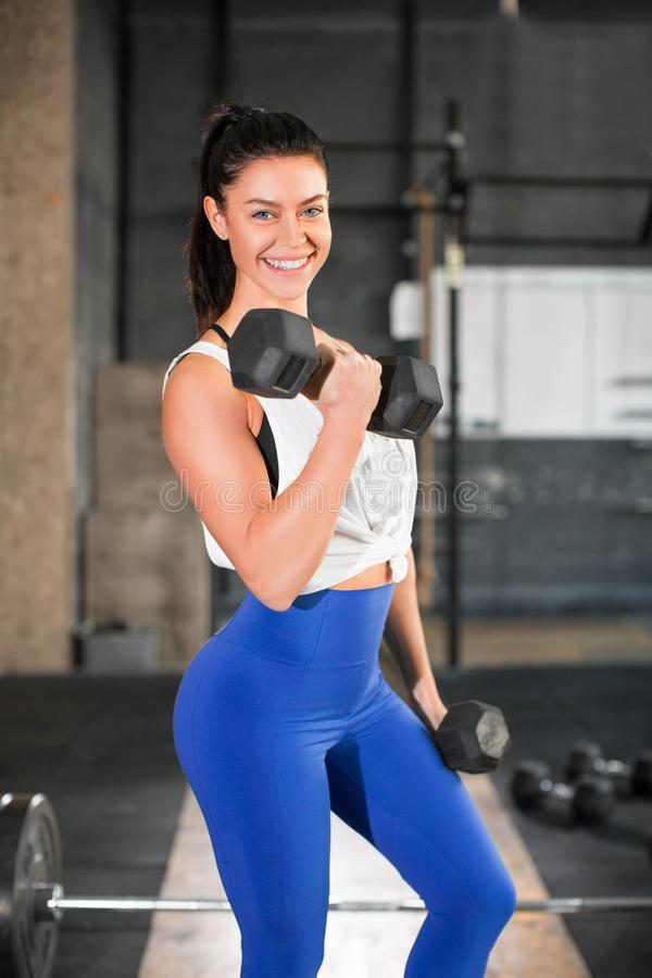 Portrait of a smiling woman with dumbbell in gym. stock photo