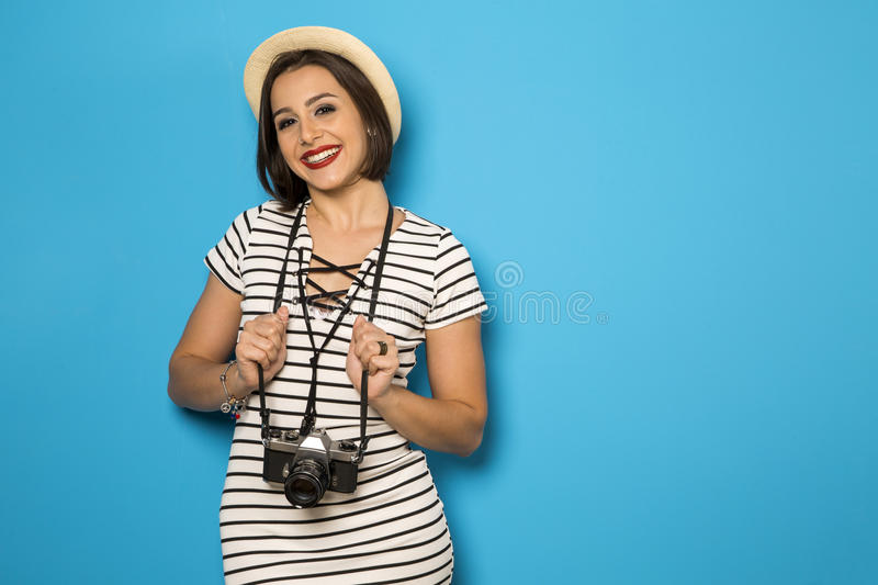 Portrait of smiling woman fashion with old camera on blue background royalty free stock photos