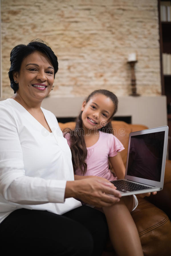 Portrait of smiling woman with granddaughter holding laptop at home. Portrait of smiling woman with granddaughter holding laptop while sitting on sofa at home stock photos