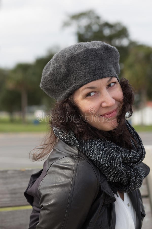 Portrait of smiling woman with grey beret. Dark scarf and knowing smile stock images